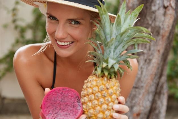 Mulher feliz e sorridente com pele sã, tem sorriso largo, come frutas exóticas, tem boa recreação em país tropical, passa as férias de verão em lugar paradisíaco, recebe vitaminas. alimentação saudável Foto gratuita