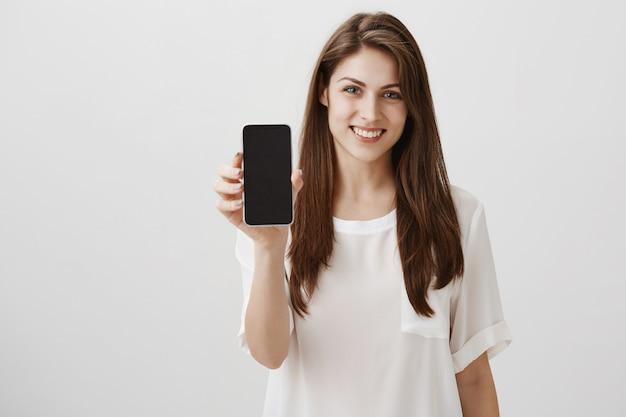 Mulher feliz e sorridente mostrando uma tela de celular, um aplicativo recomendado ou um site de compras Foto gratuita