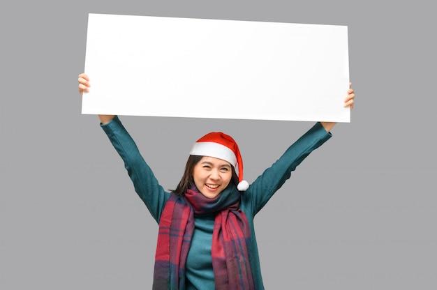 Mulher feliz em pano de tema de natal com chapéu de papai noel, apresentando faixa em branco Foto Premium