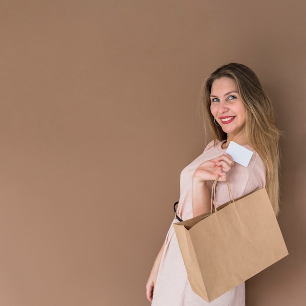 Mulher feliz em pé com a sacola de compras e cartão de crédito Foto gratuita