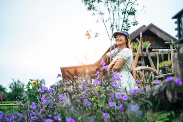 Mulher feliz em pé no jardim nos trilhos de madeira Foto gratuita