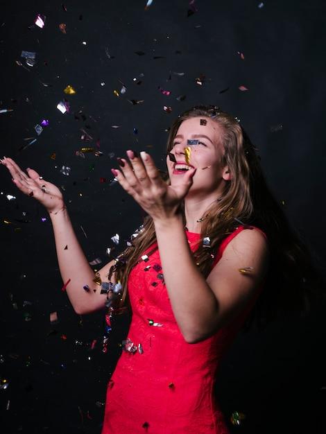 Mulher feliz em pé rosa sob lantejoulas Foto gratuita