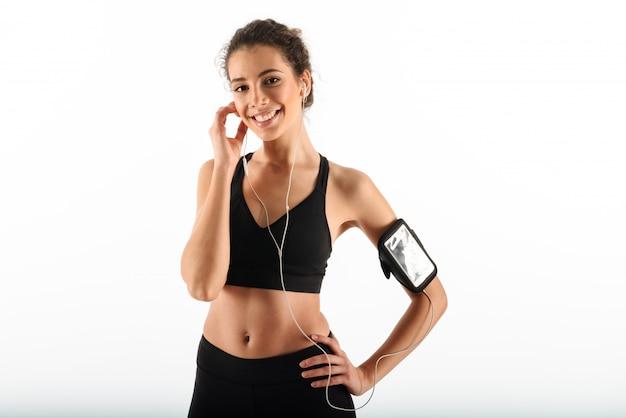 Mulher feliz encaracolado morena fitness segurando o braço no quadril e ouvir música Foto gratuita