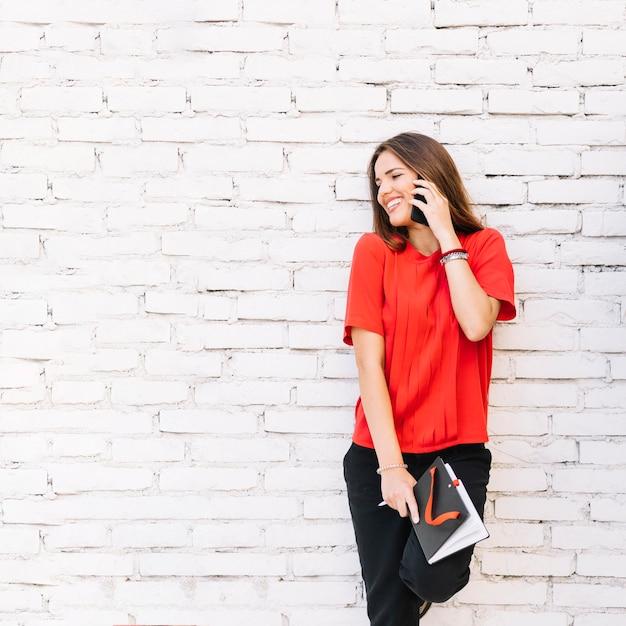 Mulher feliz falando no celular contra brickwall Foto gratuita