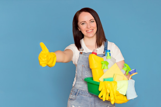 Mulher feliz faxineira com um balde cheio de detergente colorido em luvas de borracha, Foto Premium