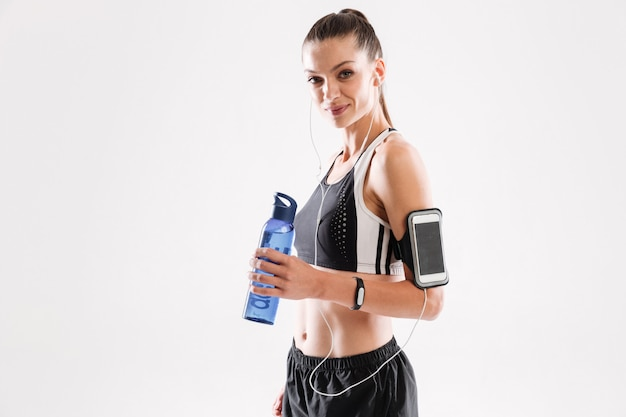 Mulher feliz fitness em fones de ouvido em pé e segurando a garrafa de água Foto gratuita