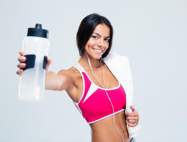 Mulher feliz fitness segurando uma garrafa com água Foto Premium