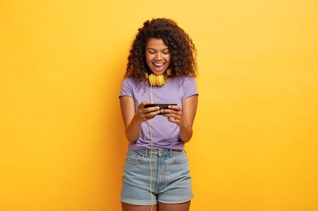 Mulher feliz jogando smartphone, obcecada por jogos online, passa seu tempo livre com tecnologias modernas Foto gratuita