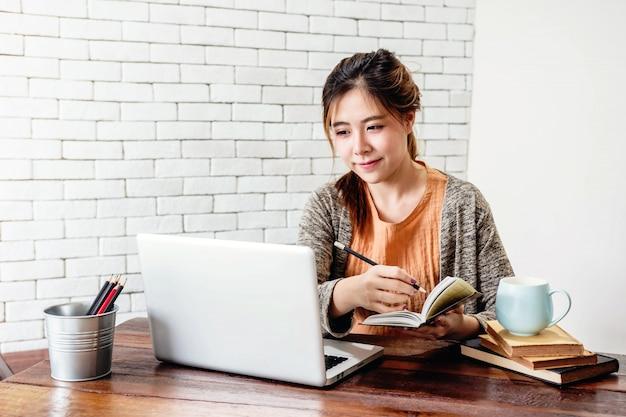 Mulher feliz jovem freelancer trabalhando no computador portátil Foto Premium