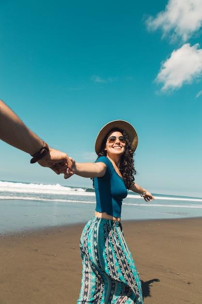 Mulher feliz levando o homem através da areia da praia Foto gratuita