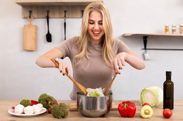 Mulher feliz, misturando a tigela com salada Foto gratuita