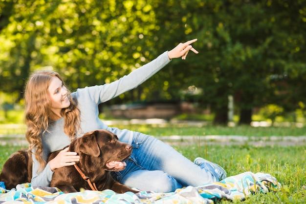 Mulher feliz mostrando algo para seu cachorro no jardim Foto gratuita