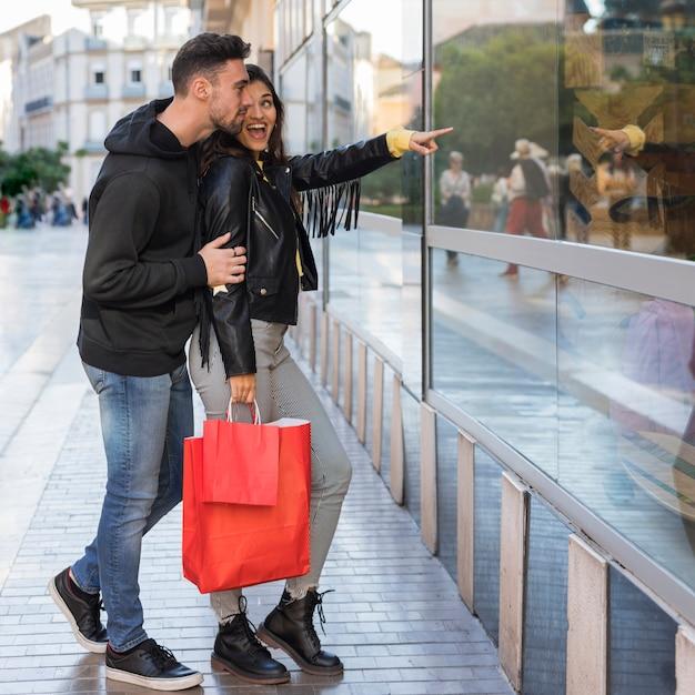 Mulher feliz, mostrando, ligado, vitrina, para, homem jovem Foto gratuita