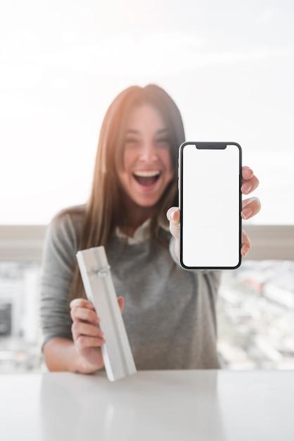Mulher feliz, mostrando, smartphone Foto gratuita