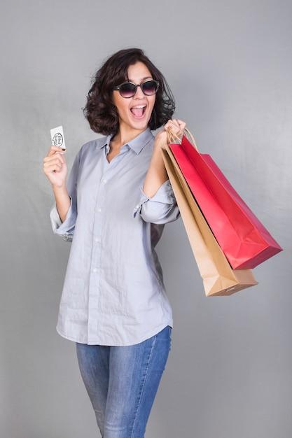 Mulher feliz na camisa com malas e cartão de crédito Foto gratuita