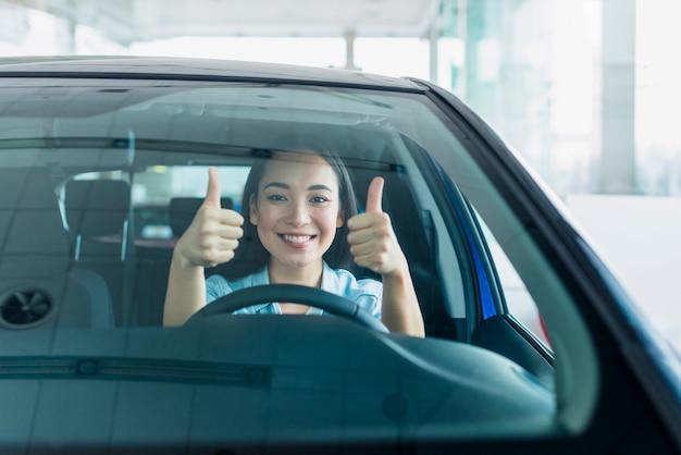 Mulher feliz na concessionária de carros Foto gratuita