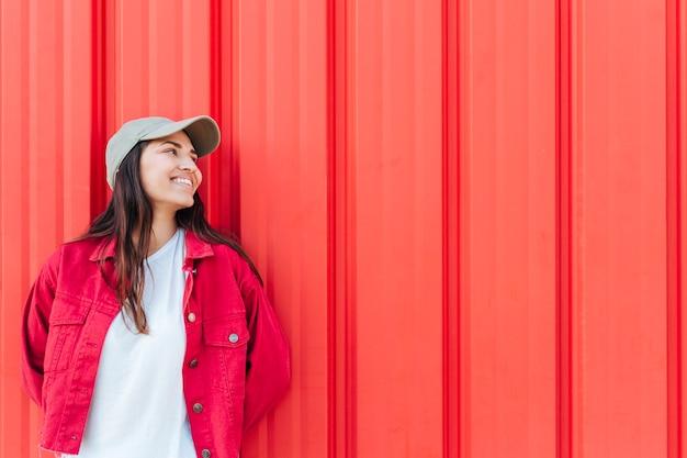 Mulher feliz na moda a desviar o olhar contra o fundo vermelho Foto gratuita