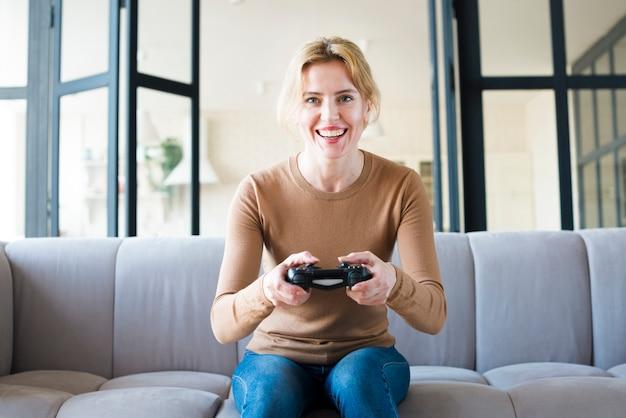 Mulher feliz no sofá jogando consola de jogos Foto gratuita