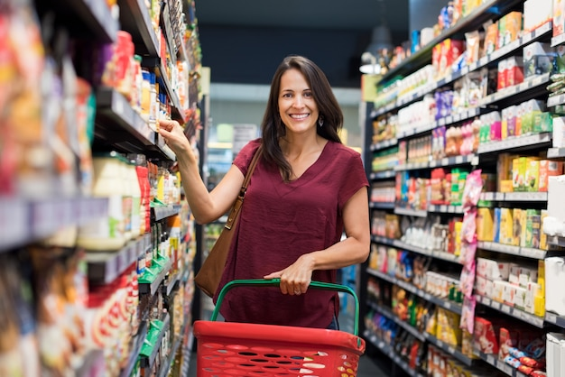 Mulher feliz no supermercado Foto Premium