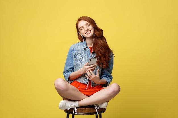 Mulher feliz nos fones de ouvido que escuta a música e que canta ao sentar e ao guardar o telefone celular. Foto Premium