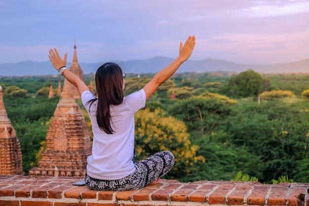 Mulher feliz nova que viaja, viajante asiático no pagode e vista de templos antigos bonitos, marco e popular para atrações turísticas em bagan, myanmar. conceito de viagens na ásia Foto Premium