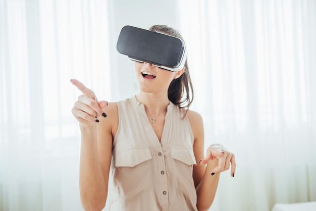 Mulher feliz obtém experiência com o uso de headset de realidade virtual de óculos vr em um ambiente brilhante Foto Premium