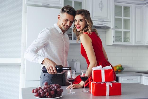 Mulher feliz olhando enquanto seu homem derramando vinho em copos em casa Foto gratuita