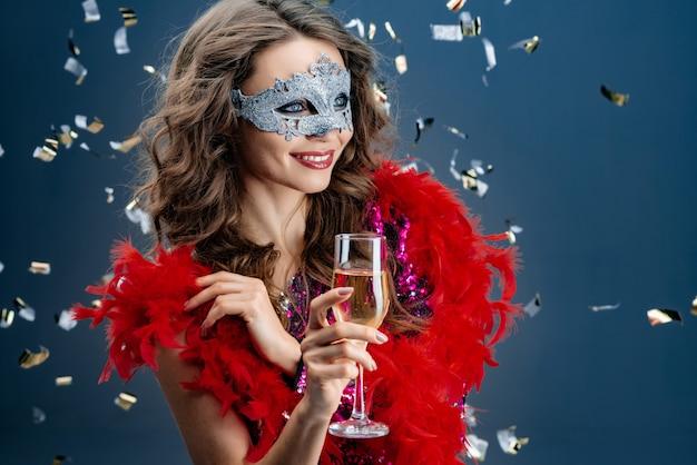 Mulher feliz parece longe em uma máscara veneziana em uma festa em um fundo festivo com ouropel Foto Premium