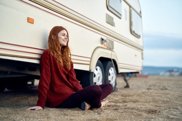 Mulher feliz perto de uma van de viagens perto do mar Foto Premium