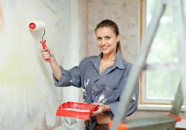 Mulher feliz pinta parede Foto gratuita