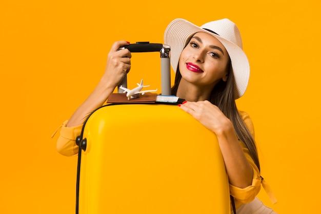 Mulher feliz posando com bagagem e estar pronto para férias Foto gratuita