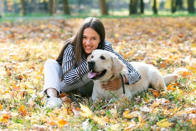 Mulher feliz posando com cachorro fofo Foto gratuita