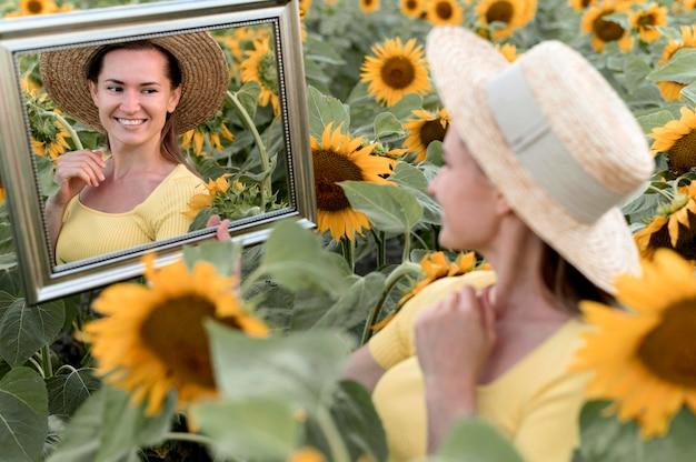 Mulher feliz posando com espelho Foto gratuita