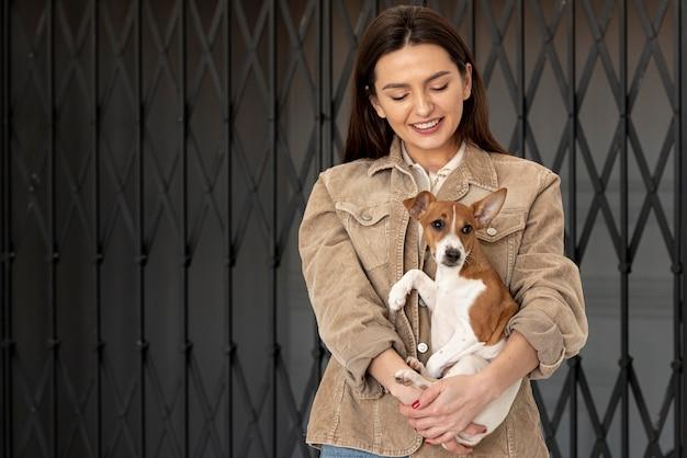 Mulher feliz posando com seu cachorro Foto gratuita