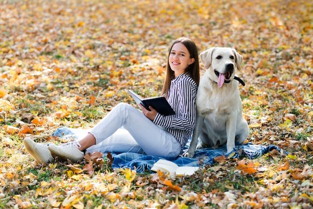 Mulher feliz posando com seu labrador Foto gratuita