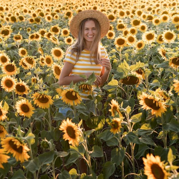 Mulher feliz posando em campo de girassol Foto gratuita