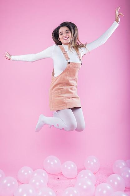 Mulher feliz pulando no chão com balões de ar Foto gratuita