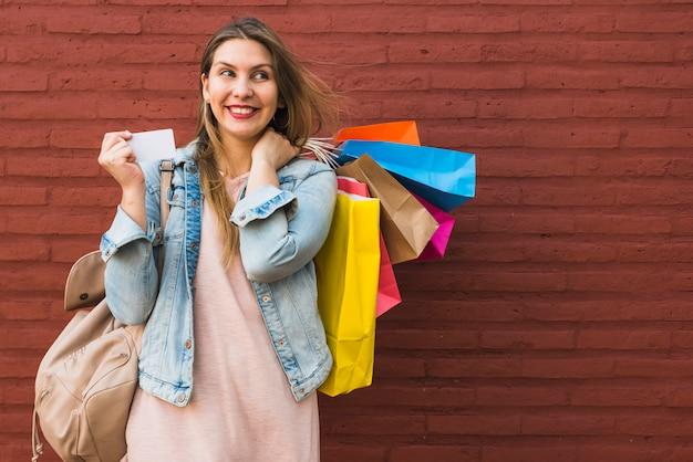 Mulher feliz que está com sacos de compras e cartão de crédito na parede de tijolo vermelho Foto gratuita