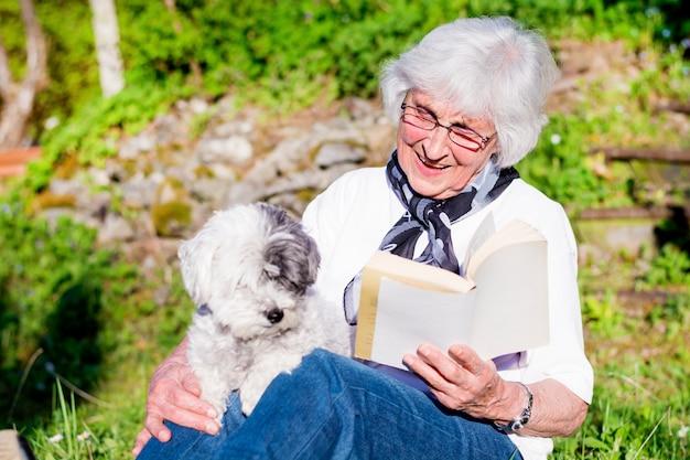 Idosa lendo para seu cachorro