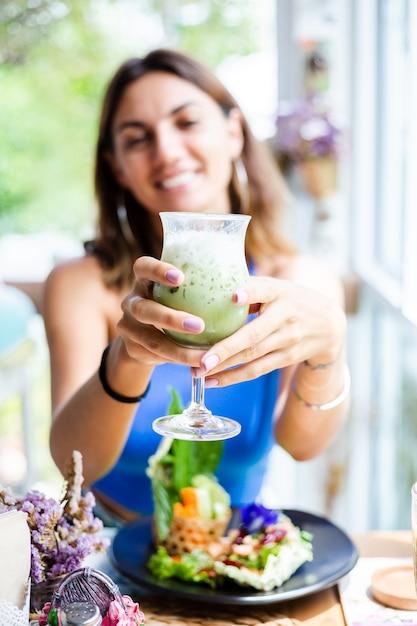 Mulher feliz segurando chá verde matcha japonês com gelo em um copo no café mulher com bebida antioxidante saudável no café bonito de verão Foto gratuita