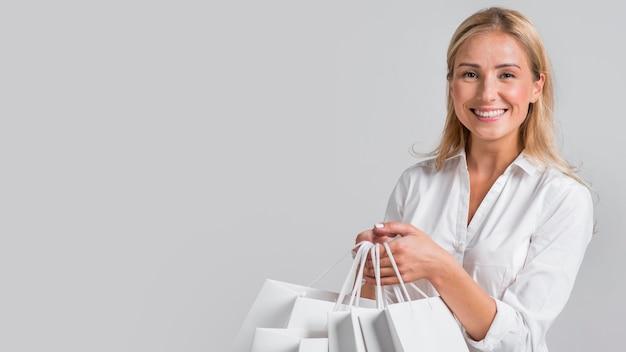 Mulher feliz segurando muitas sacolas de compras Foto gratuita