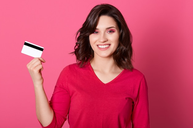 Mulher feliz, segurando o cartão de crédito nas mãos, olhando para a câmera com um sorriso, ter muito dinheiro para compras on-line, vestindo camisa casual vermelha, tem cabelo escuro. Foto gratuita