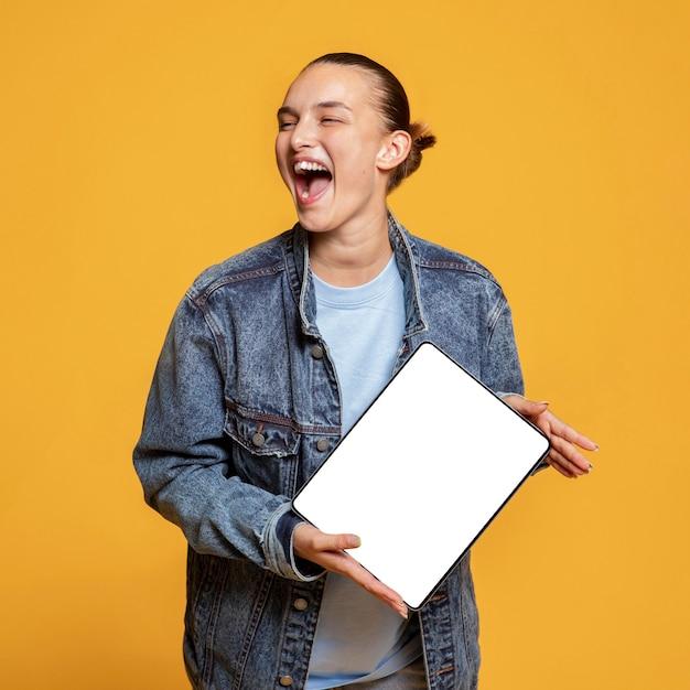 Mulher feliz segurando tablet Foto gratuita