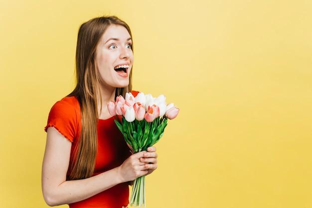 Mulher feliz, segurando um buquê de tulipas com espaço de cópia Foto gratuita