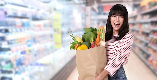 Mulher feliz segurando um saco de papel cheio de legumes frescos e baguetes no supermercado Foto Premium
