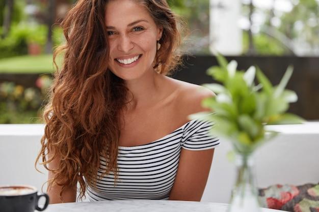 Mulher feliz sentada em uma cafeteria Foto gratuita