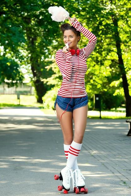 Mulher feliz sobre o patins no parque Foto Premium