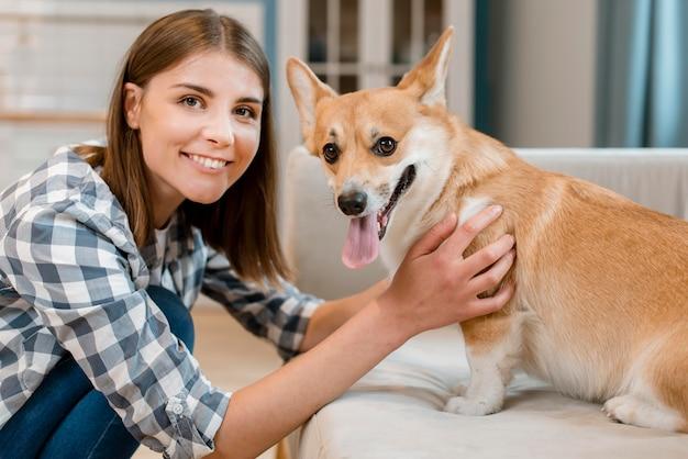 Mulher feliz sorrindo enquanto posava com seu cachorro Foto gratuita