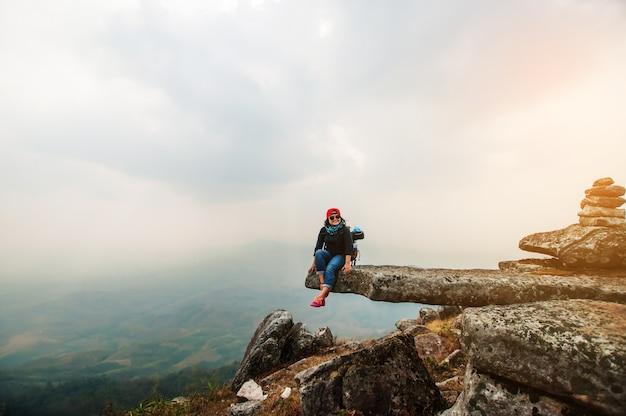 Mulher feliz sorrir na montanha superior com céu azul Foto Premium