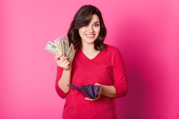 Mulher feliz tem carteira e dinheiro nas mãos, pensa em como gastar seu salário. menina morena estar feliz em ir às compras Foto Premium